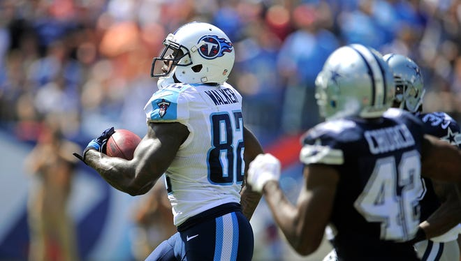 Titans tight end Delanie Walker outruns two Dallas defenders on his way to a 61-yard touchdown in the third quarter Sunday.