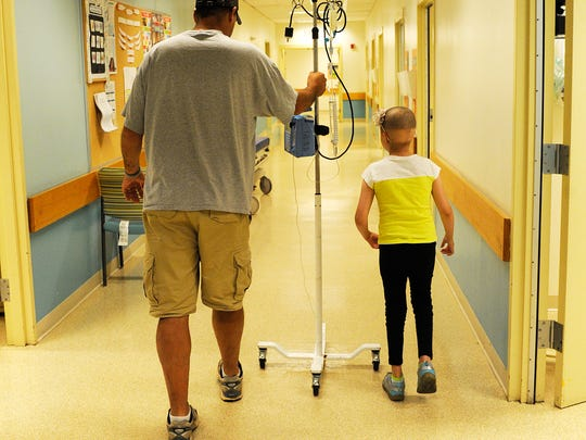 Norah walks with her father to the bathroom with her IV pole on July 5 at the University of Virginia Medical Center. Norah went to the Charlottesville hospital that day to get chemotherapy, but her platelets were too low, so she instead got a dose of antibiotics in the hopes of receiving chemo the following week.