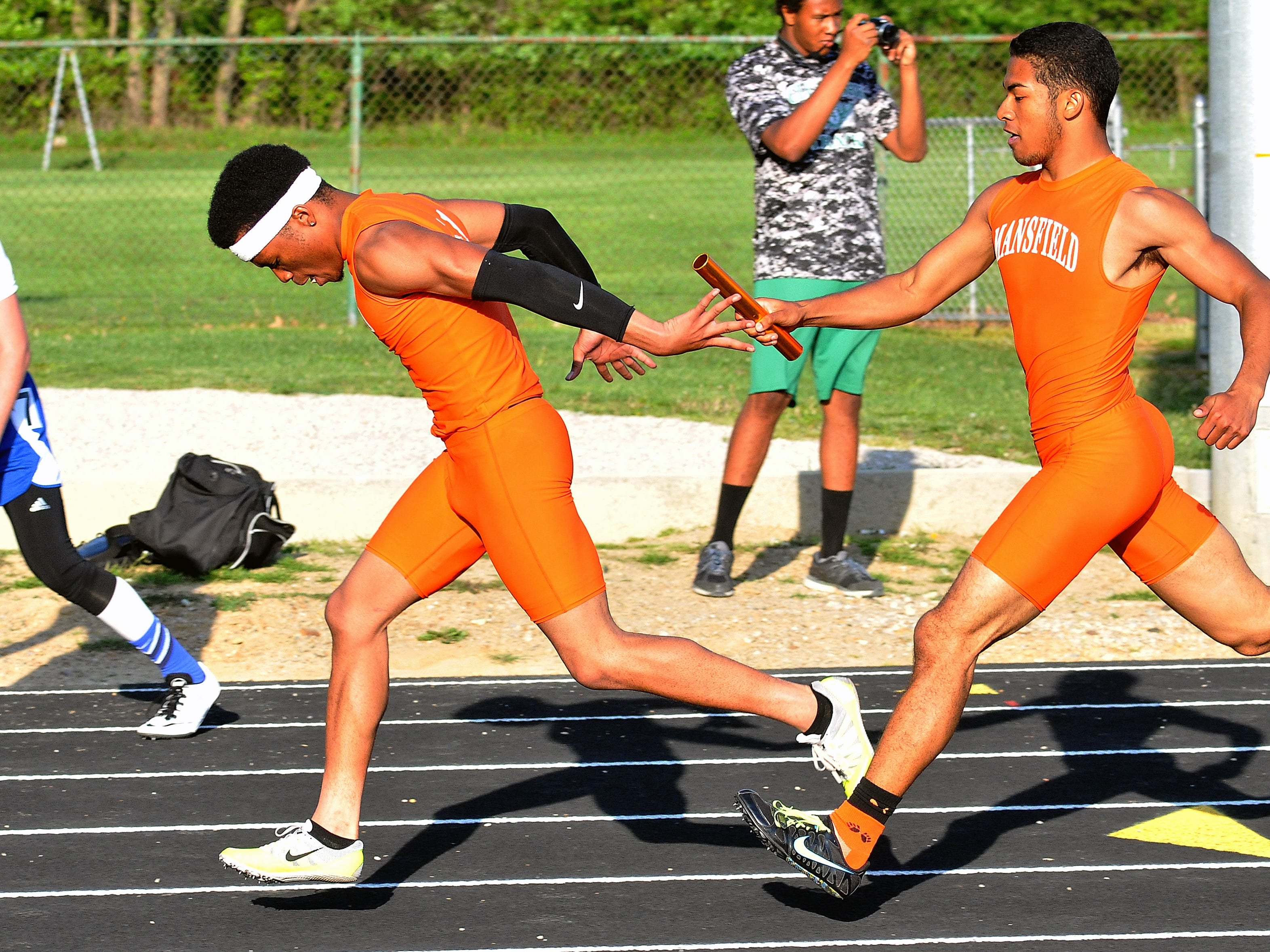 Mansfield Senior's George Swarn hands off to Jacquez Wellington during the boys 4X200 Meter Relay at Madison High School Friday.
