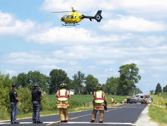 Emergency responders watch as a ThedaStar helicopter