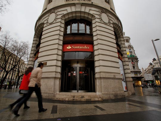 People walk into a Banco Santander office on Feb. 2,