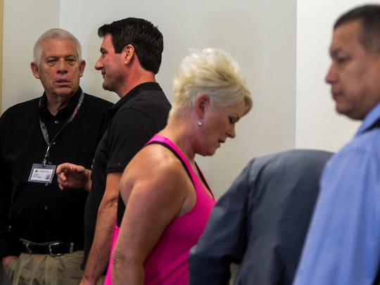 Law-enforcement officials and bidders gather at the