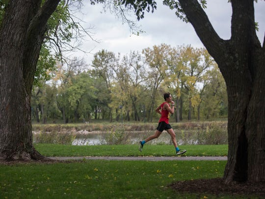 A runner circles Gray's Lake during the IMT Des Moines Marathon on Sunday, Oct. 15, 2017.