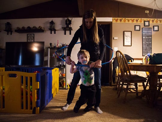 Tatum Woods, one of a very small number of Iowans with the rare genetic disorder Kabuki syndrome, walks with the assistance of a hula hoop and his physical therapist Emily Tiedtke in his home on Tuesday, Jan. 30, 2018, in Vinton. Woods has outgrown a special walker he once used and cannot get new one because Amerigroup, his medicaid provider, will only reimburse a fraction of the cost.