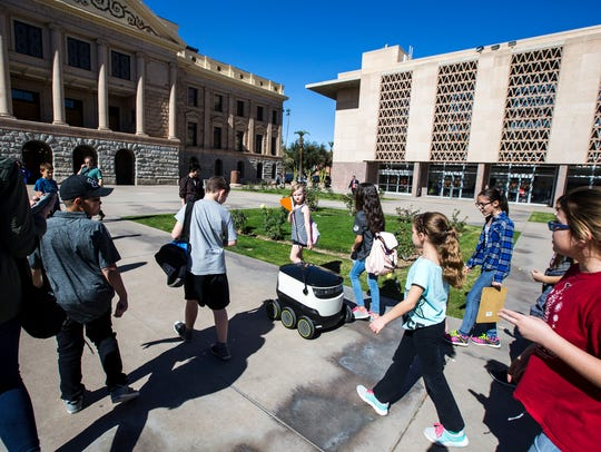 Schoolchildren walk by a robot on Feb. 7, 2018, at