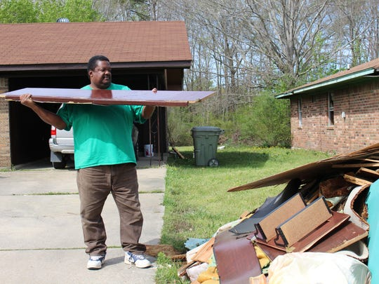 Terrence Lewis throws a wood plank from a piece of furniture on a scrap pile at his home near Tanglewood Subdivision.