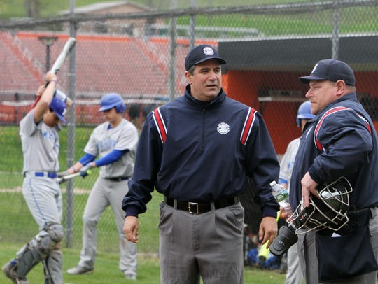 From left, Umpire Ray Sarcone talks with his partner