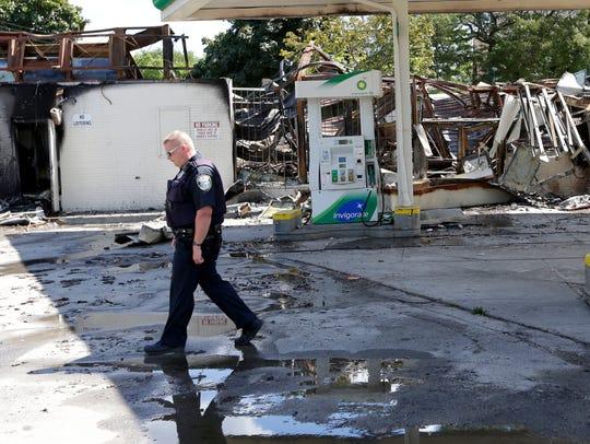A Milwaukee police officer walks near the burned gas