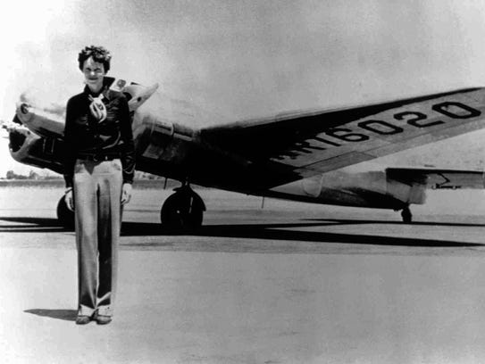 Amelia Earhart stands next to a Lockheed Electra 10E