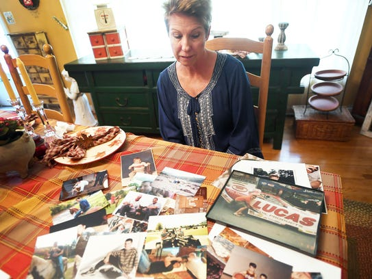 Phyllis Crawford looks through photographs of her son,