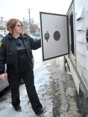 Humane officer Ashlee Bishop, 26, of Wausau, opens the kennel built in her truck Friday afternoon, Jan. 16, 2015, at the Wausau Police Department.