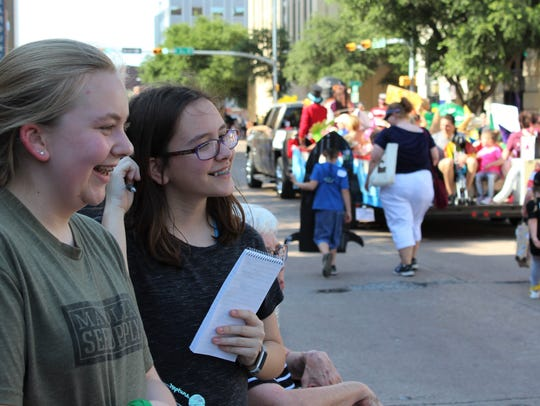 A newspaper reporter is allowed to have fun during an assignment, so Katherine Strader, right, of Tyler, and her Abilene cousin Olivia Law, giggle at the entries in Thursday's Storybook Parade in downtown Abilene.