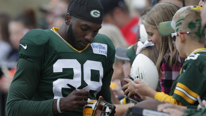 Packers cornerback Josh Hawkins signs autographs during training camp.