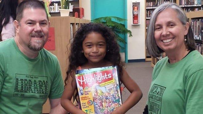 Peoria residents Gary and Tina Mlodzik with May'Ley Nguyen, 6, enjoying her book at the Grow Your Library event in Huachuca City, Ariz. in October 2015.
