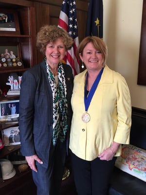 Justin Phillips (right), standing with U.S. Rep. Susan Brooks, R-Carmel, received the Jefferson Award at a national ceremony in Washington, D.C., for her work with the nonprofit organization Overdose Lifeline.
