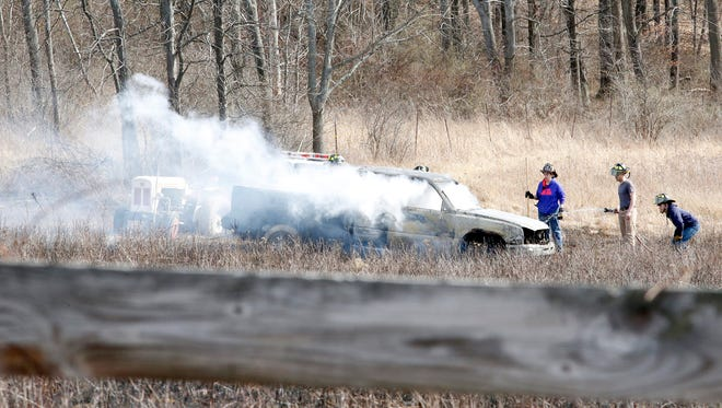 Fire crews tend to the truck they believe caused a brush fire Wednesday afternoon that burned around three acres of land on Comfort Hill Road in Wellsburg.