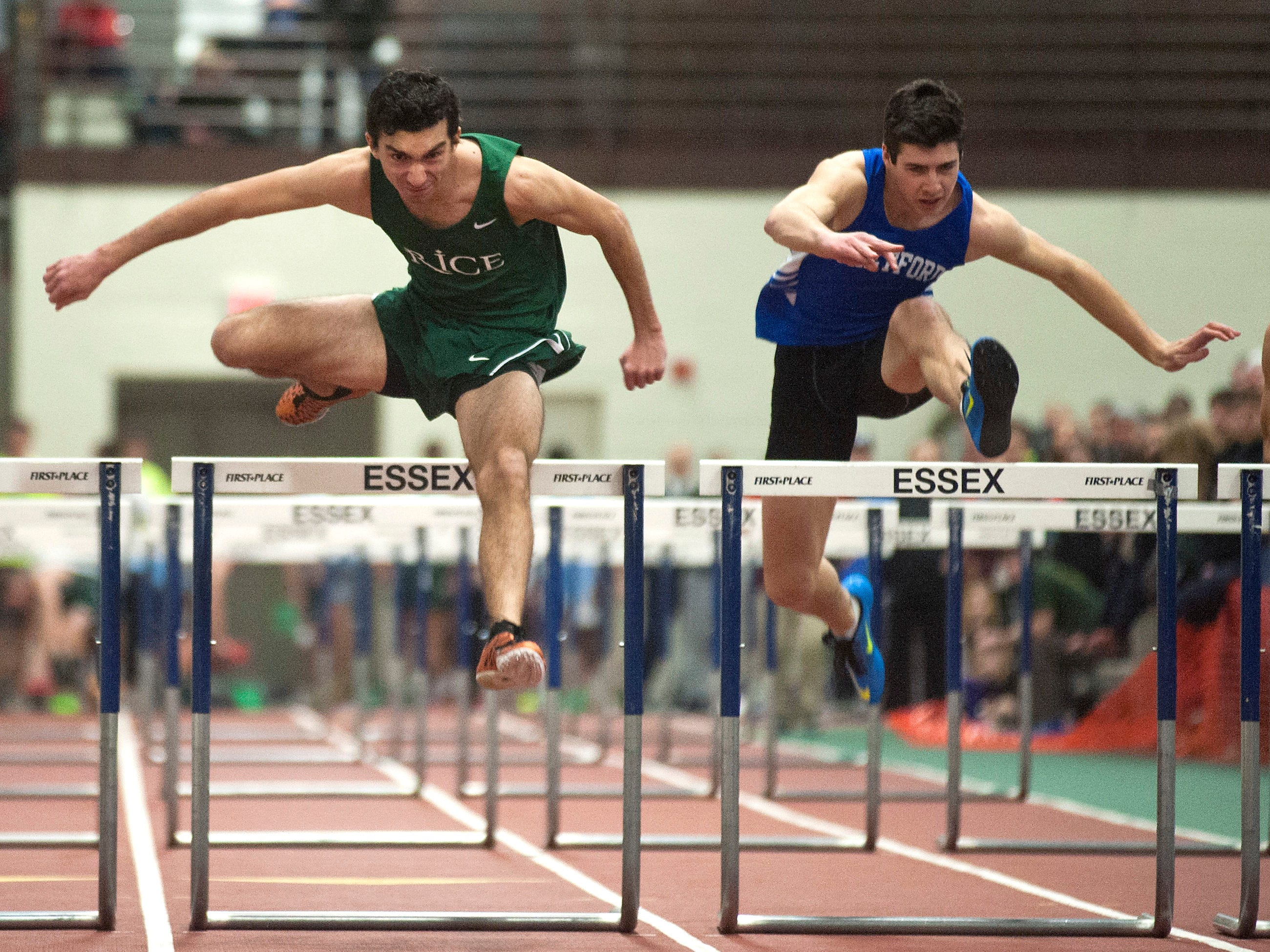 Rice's Griffin Cunningham, left, clears the final hurdle en route to edging Thetford's Cole Chapman, right, for the Division II boys 55-meter hurdles championship on Saturday at Norwich University.