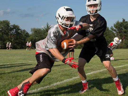 Senior quarterback Ben Olson, right, hands off to senior