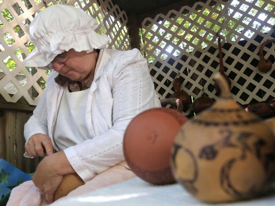 Lynn Rehm, of Big Prairie, works on carving gourds at the Prairie Peddler Festival near Butler on Saturday.