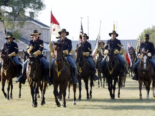 Participants in the National Cavalry Competition circle the parade ground of Fort Concho Historic Landmark.