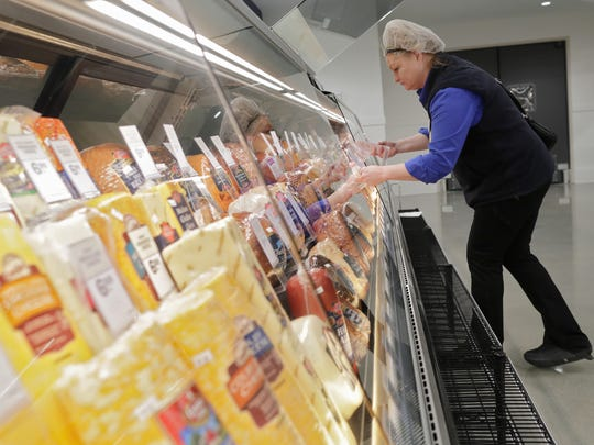 Debbie Meyer prepares a deli display at the new Meijer store in Grand Chute.
