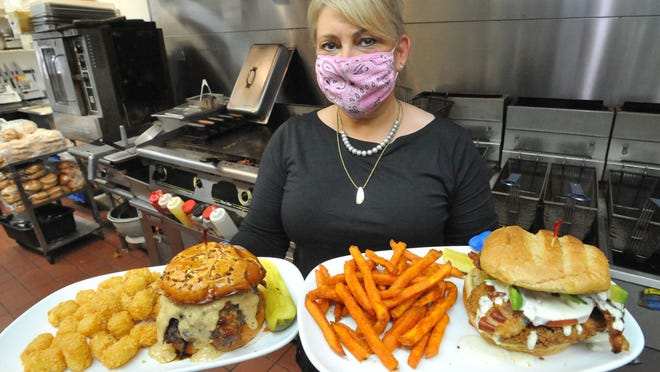 KKatie's Burger Bar co-owner Kate McSorley serves up a horseradish peppercorn burger, left, and a classic buttermilk chicken sandwich at KKatie's Burger Bar in Plymouth, Friday, June 12, 2020. Tom Gorman/For The Patriot Ledger