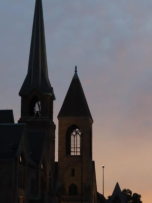 Steeples of the First United Methodist Church, 421 Washington St., and First Presbyterian Church, 321 N. Fifth St., are silhouetted by the setting sun Tuesday in downtown Burlington.