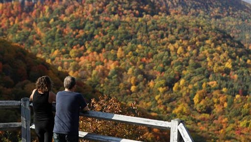 A couple takes in the view of fall colors at John Boyd Thacher State Park on Tuesday, Oct. 18, 2016, in Voorheesville, N.Y.