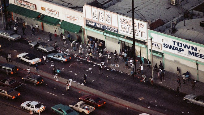 In this April 29, 1992 file photo, people enter and leave a swap meet in South Central Los Angeles. Violence broke out in the area after four Los Angeles police officers were acquitted on all but one charge for the videotaped beating of motorist Rodney King.