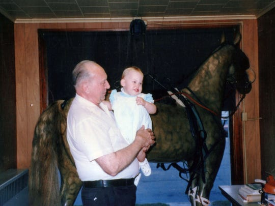 William Zastoupil Jr. holds his granddaughter, Sara Zastoupil, while standing in front of the horse in the window on South Eighth Street. William Jr. owned and ran the company after his father, William Sr., and before he the company to his life-long employee, Emil Stauber, in 1989.