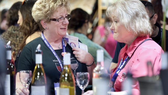 Terri Cothron, left, and Geordie Ebert sample wines at Janeen's Furniture Gallery during the Downtown Visalia Wine Walk on Thursday, April 7, 2016.