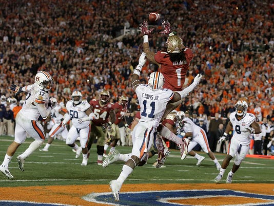 FILE - In this  Jan. 6, 2014, file photo, Florida State's Kelvin Benjamin catches the game-winning touchdown pass during the second half of the NCAA BCS National Championship college football game against Auburn in Pasadena, Calif. The Tigers jumped out to a 21-3 first-half lead on Heisman winner Jameis Winston and the Seminoles. Winston connected with Kelvin Benjamin on a 2-yard TD pass with 13 seconds left to give Florida State the win in the final NCS championship game. (AP Photo/Chris Carlson, File)