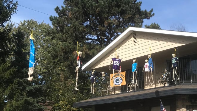 A Halloween display in Okauchee has skeletons hanging and wearing different NFL team jerseys.