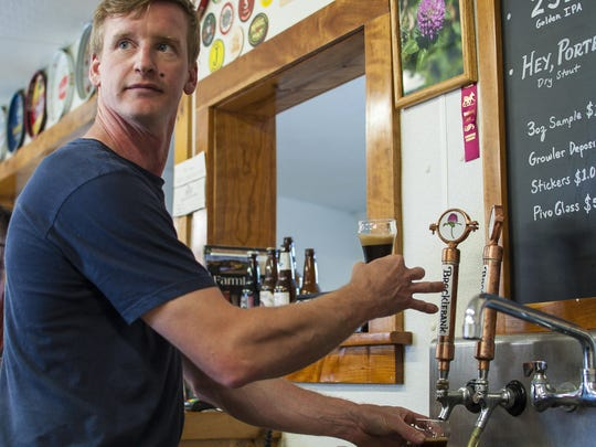 Ben Linehan, co-owner with Anne Lineman of Brocklebank Brewery in Tunbridge, fills glasses at the brewery's tasting room on Friday, July 15, 2016.