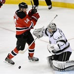 Los Angeles Kings goaltender Jonathan Quick, right, stops the puck as New Jersey Devils' Adam Henrique (14) looks on during the third period Monday, March 23, 2015, in Newark, N.J. The Kings won 3-1.