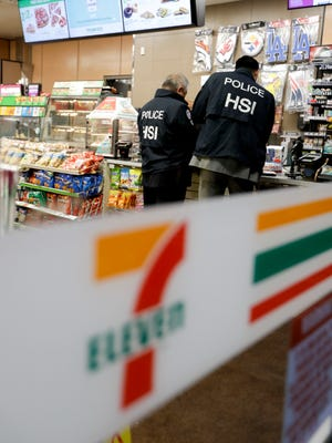 U.S. Immigration and Customs Enforcement agents serve an employment audit notice at a 7-Eleven convenience store, Jan. 10, 2018, in Los Angeles.