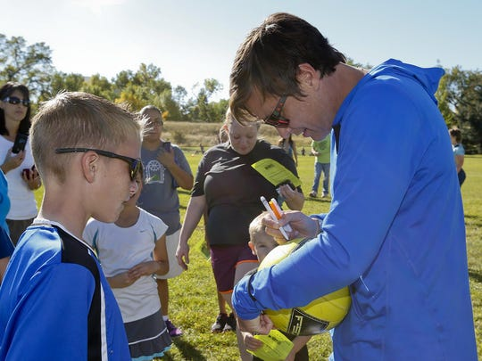 Soccer star Abby Wambach autographs a soccer ball for Gavin Groshelle, 11, at the Elks Riverside Park Saturday during a Come Out and Play 2014 with Abby Wambach sponsored by Get Fit Great Falls.