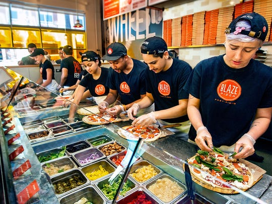Assembly line format of Blaze Pizza in action building customer designed pizzas