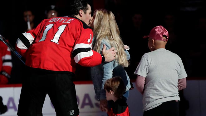 New Jersey Devils center Brian Boyle (11) kisses his wife, Lauren Bedford, after he participated in the ceremonial puck drop during the first period of an NHL hockey game against the Vancouver Canucks, Friday, Nov. 24, 2017, in Newark.