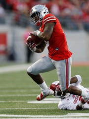 Ohio State safety Malik Hooker escapes the grasp of Indiana running back Devonte Williams after intercepting a pass during a game in Columbus, Ohio, on Oct. 8, 2016.