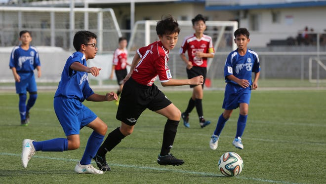 Wings Red's Rintaro Nishioka attempts to get past Guam Shipyard Wolverines' Yan Ortiz during a U13 Division semifinal match of the Aloha Maid Minetgot Cup Elite Youth Soccer League Saturday at the Guam Football Association National Training Center. Wings Red won 2-0 to advance to the championship match set for Nov. 11 against the ASC Trust Islanders.