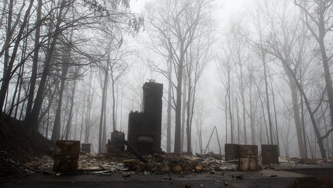 Dense fog rolls in over the site of a burned home on the northern side of Gatlinburg, Tenn., Tuesday, Dec. 6, 2016.