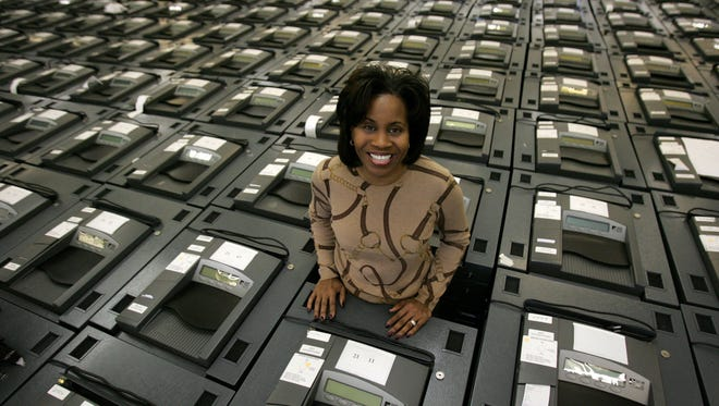 Detroit City Clerk Janice Winfrey stands in 2009 with voting machines purchased in 2006. The state plans to purchase new voting machines to replace the 10-year-old models at the center of an election night debacle.