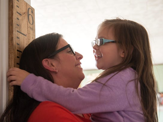 Remington Hedrick (right) measures her mother, Amber,
