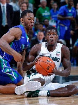 Michigan State's Eron Harris, right, grabs the ball as Florida Gulf Coast's Rayjon Tucker defends during the second half of an NCAA college basketball game Sunday,