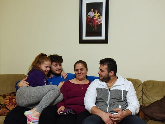 Neta Pukri sits beneath a family photo with her children, from left, Angela, age 10, Mikel, 21, and Bepin, 26.