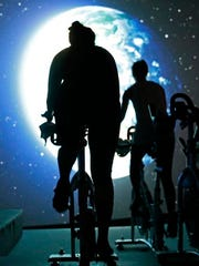 In this Jan. 3, 2017, photo, students pedal toward an image of the earth as seen from outer space in a spinning class at Brooklyn's IMAXShift in New York. i