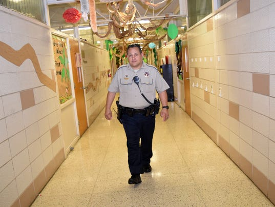 Rapides Parish Sheriff's Office deputy and school resource officer Horacio Cortez walks the hallways of Pineville Elementary during after school Thursday, Feb. 22, 2018.