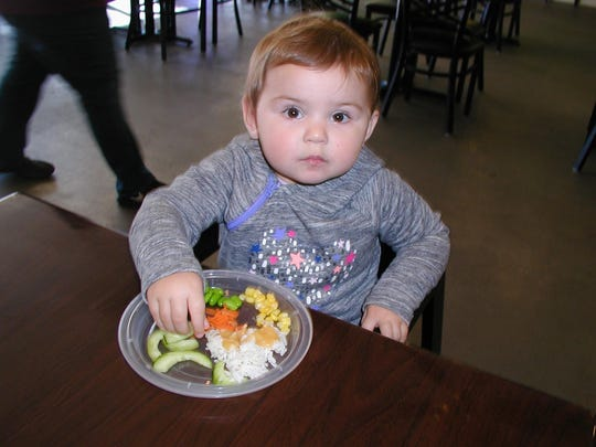"Esther Berner, 1 ½, learns healthy dining with a ""starter"" plate of rice and vegetables, which keeps her busy while mom enjoys an adult-sized poke bowl."