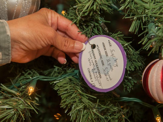 Master Sgt. Arwa Cavender, 49th Material Maintenance Squadron first sergeant, hangs an ornament on the Diamond Tree located in the Base Exchange at Holloman Air Force Base Nov. 24. The Diamond Tree program provides gifts for children at Holloman in single income homes and other families in need.